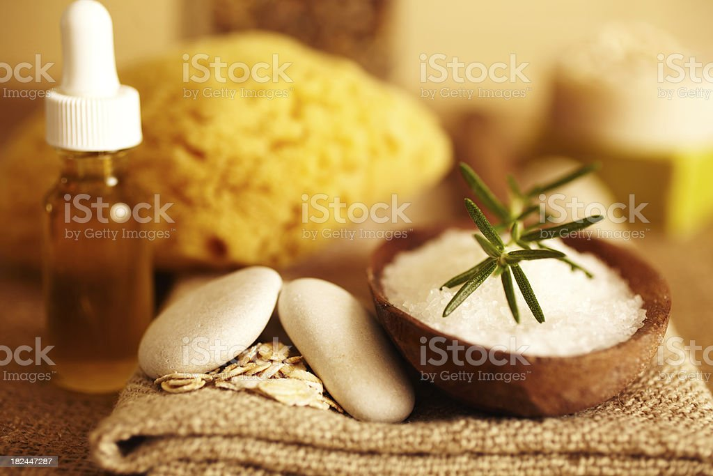 Rosemary on bath salt scrub in wooden spoon and oil stock photo