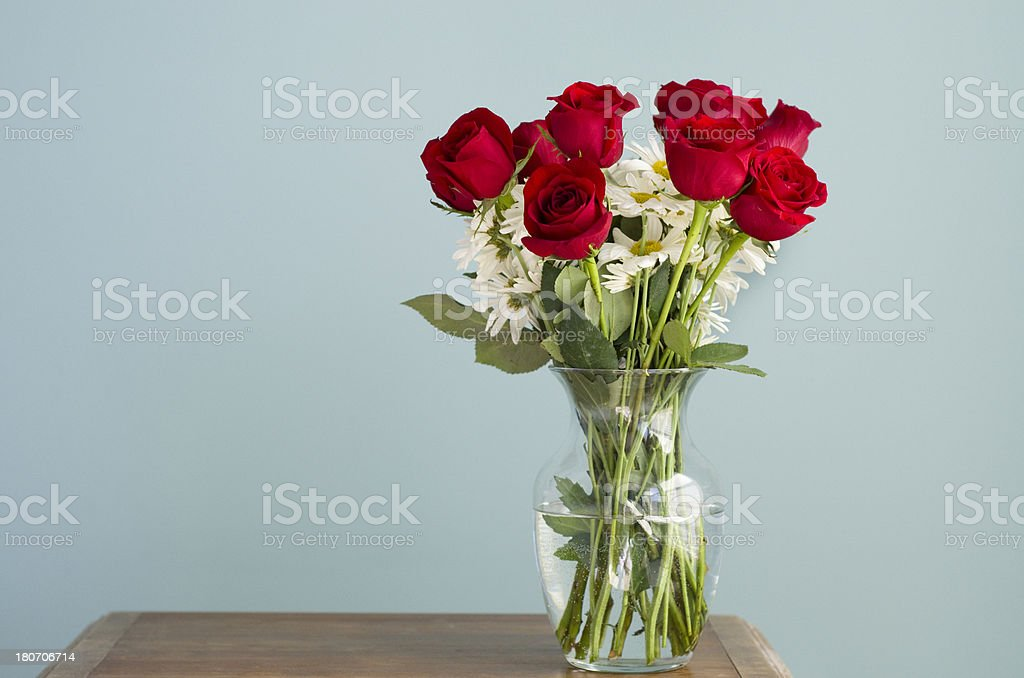 roses and daisies sit in a vase on table royalty-free stock photo