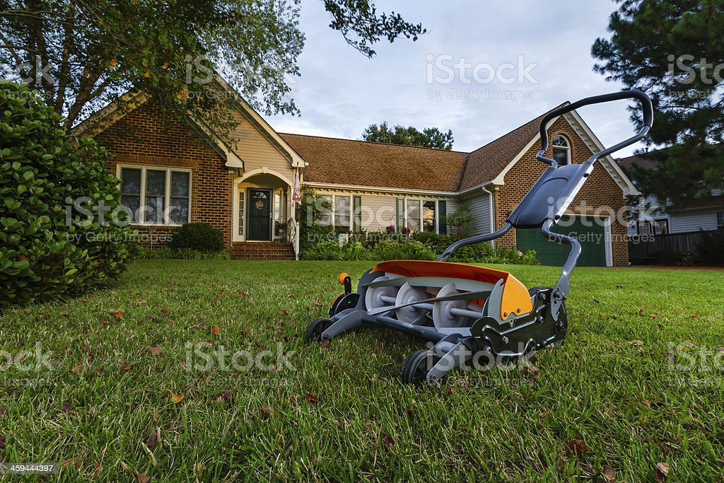 Rotary Push Mower on green lawn, brick home in background. stock photo