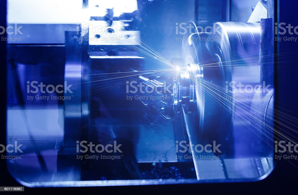 Rotating brilliant part of an automated lathe machining  metal parts stock photo