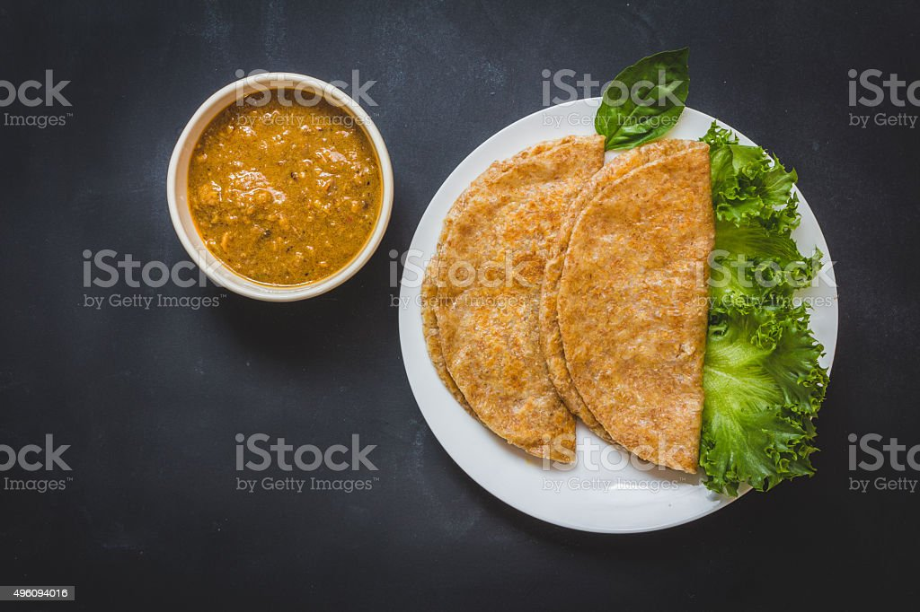 Roti and chicken curry. Top view on black background stock photo