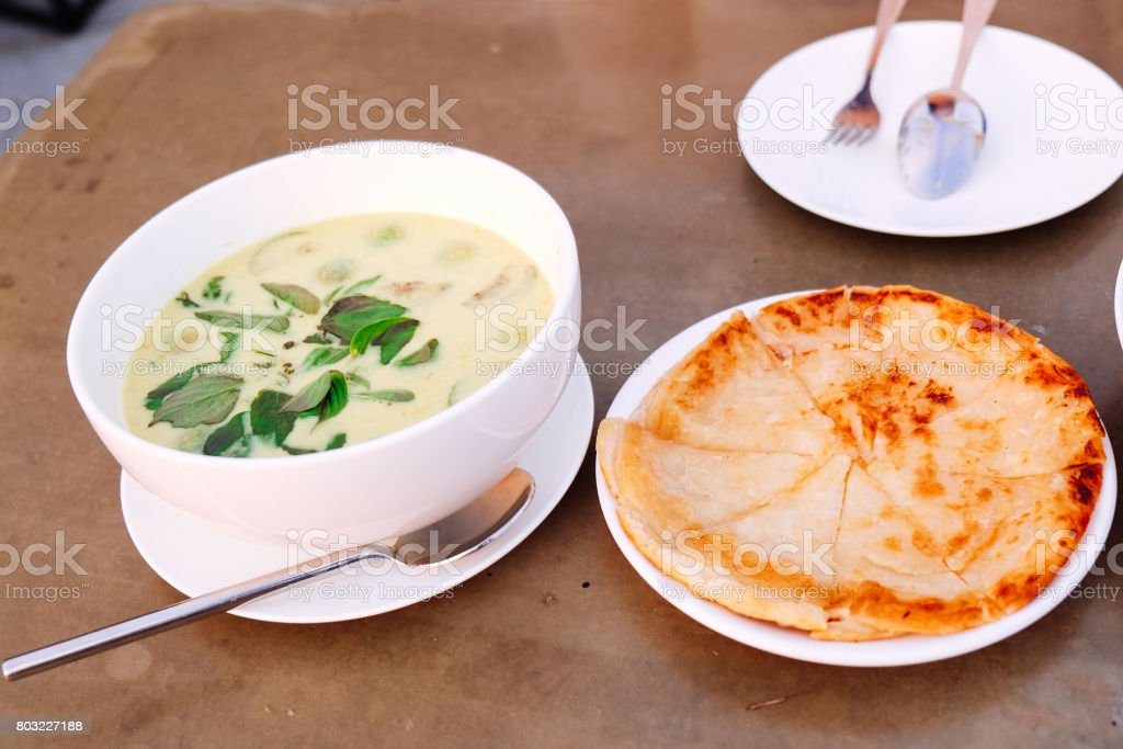 roti and thai green curry on the white dish stock photo