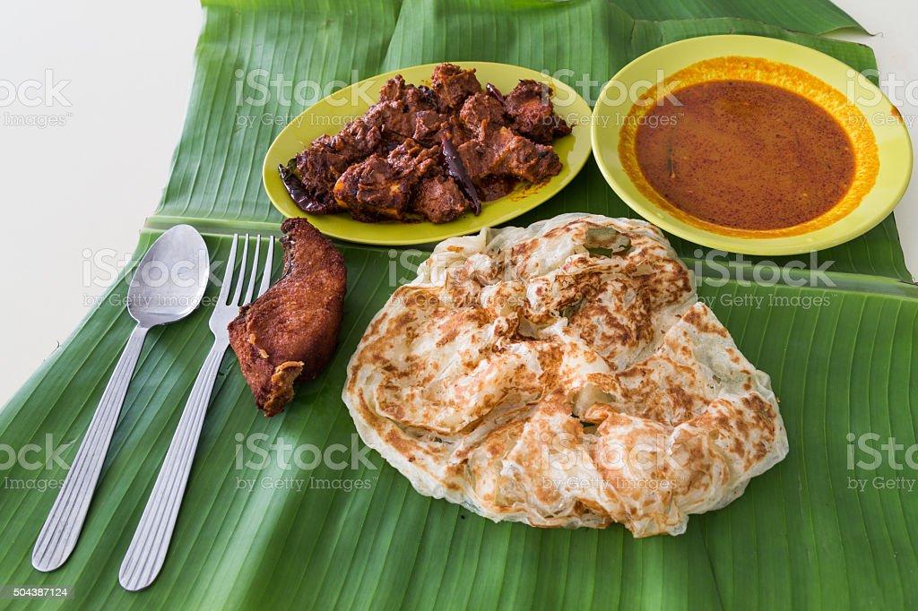 Roti prata on banana leaf with masala mutton, fish, curry stock photo