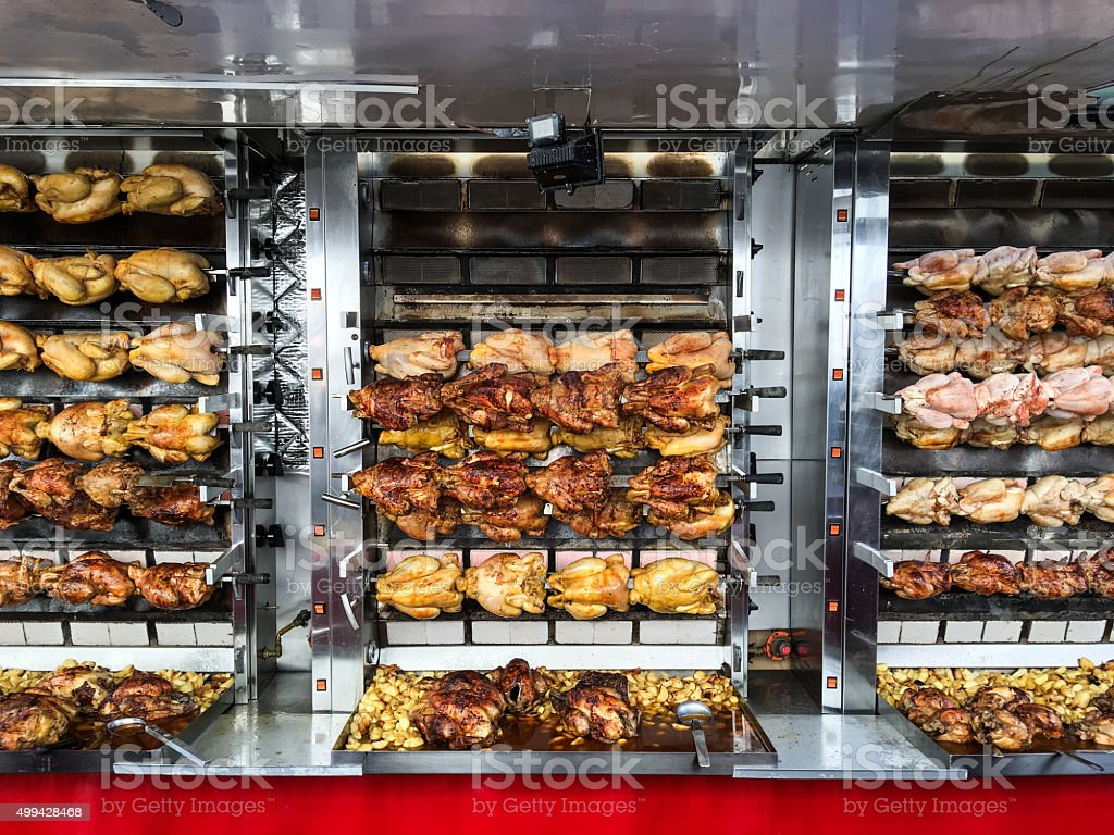 Rotisserie chickens being spit roasted at a French street market stock photo