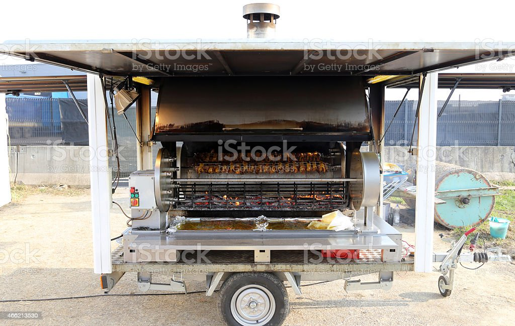 rotisserie with wheels full of cockerels and roast chickens stock photo