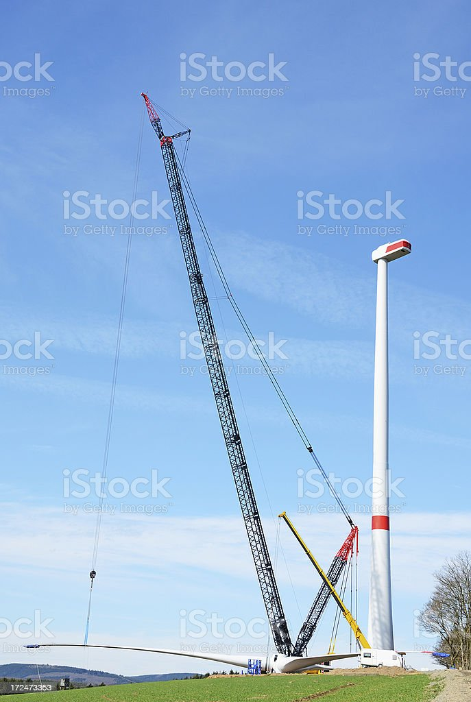Rotor blade assembly on wind turbine construction site with cranes royalty-free stock photo