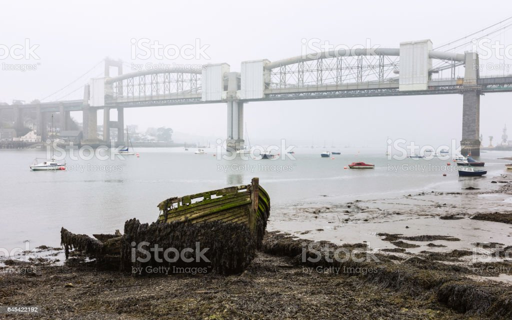 Rotten boat and Royal Albert Bridge across the river Tamar on a winter morning. stock photo