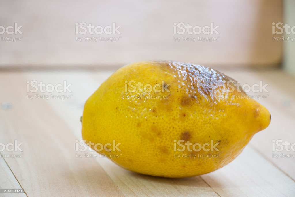 rotten lemon put on wooden table stock photo