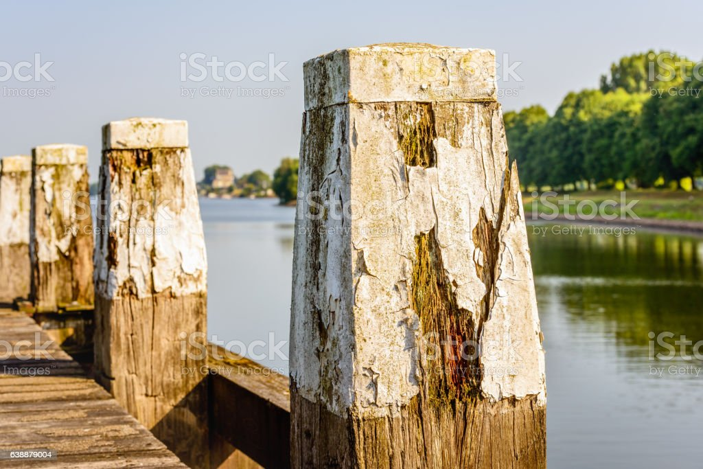 Rotten wooden pole with peeling white paint from close stock photo