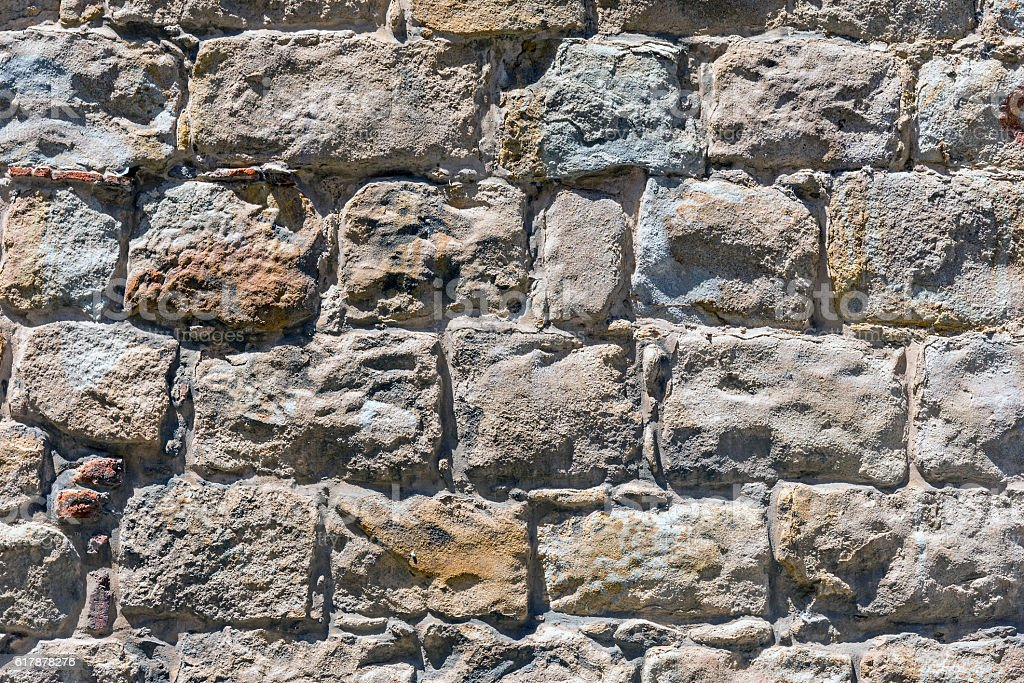 Rough brown natural stone wall stock photo