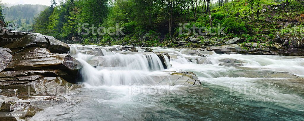rough mountain river with white foam flows among the rocks stock photo