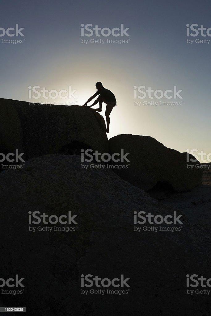 Rough terrain - Man climbing a rock against sky, silhouette royalty-free stock photo