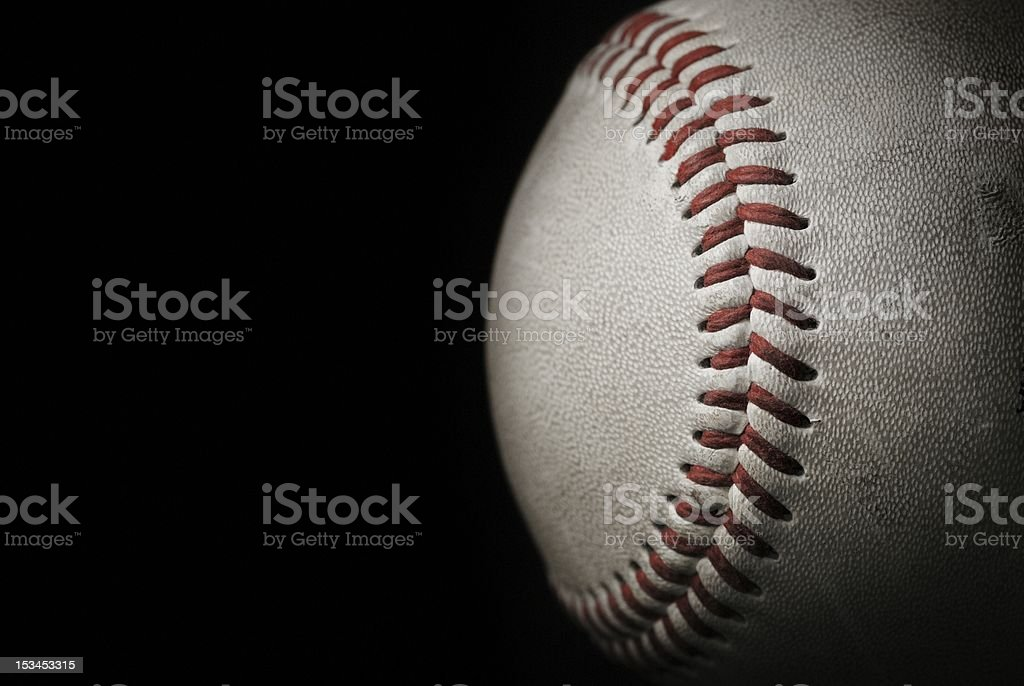 Roughed looking baseball in front of a black background stock photo