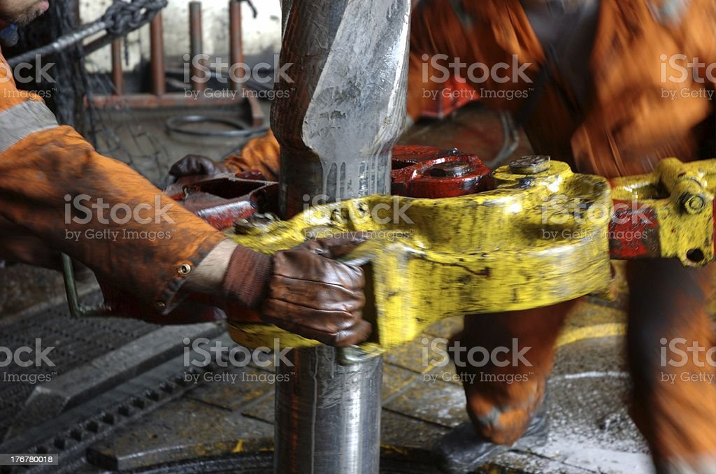 Roughnecks breaking out connection at drillfloor stock photo