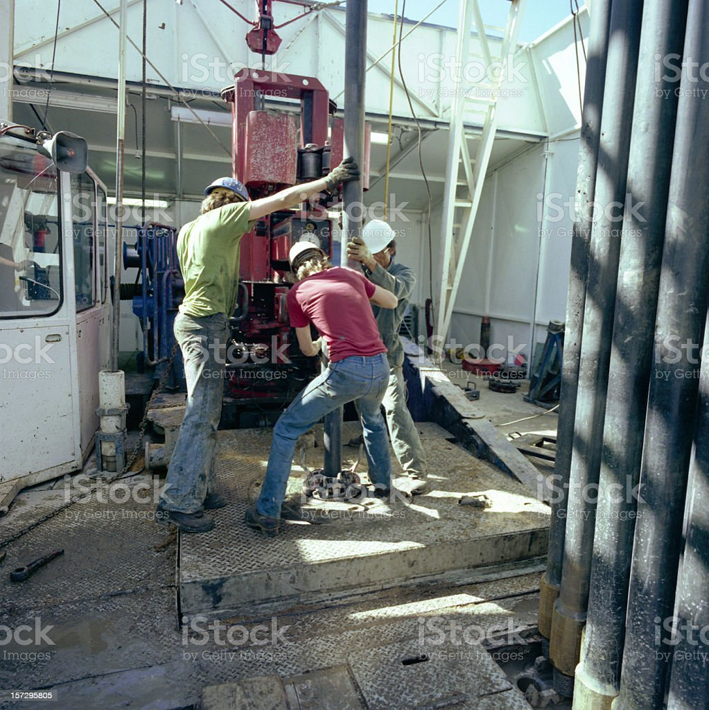 Roughnecks Pulling Pipe stock photo