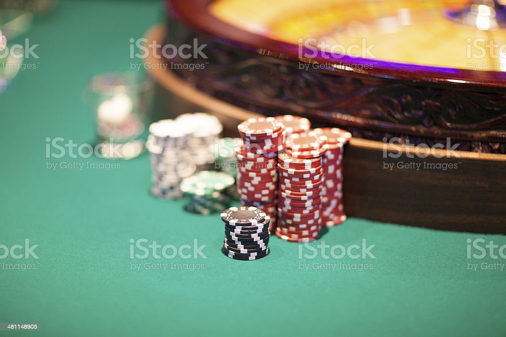 Roulette wheel with a stack of chips in casino royalty-free stock photo