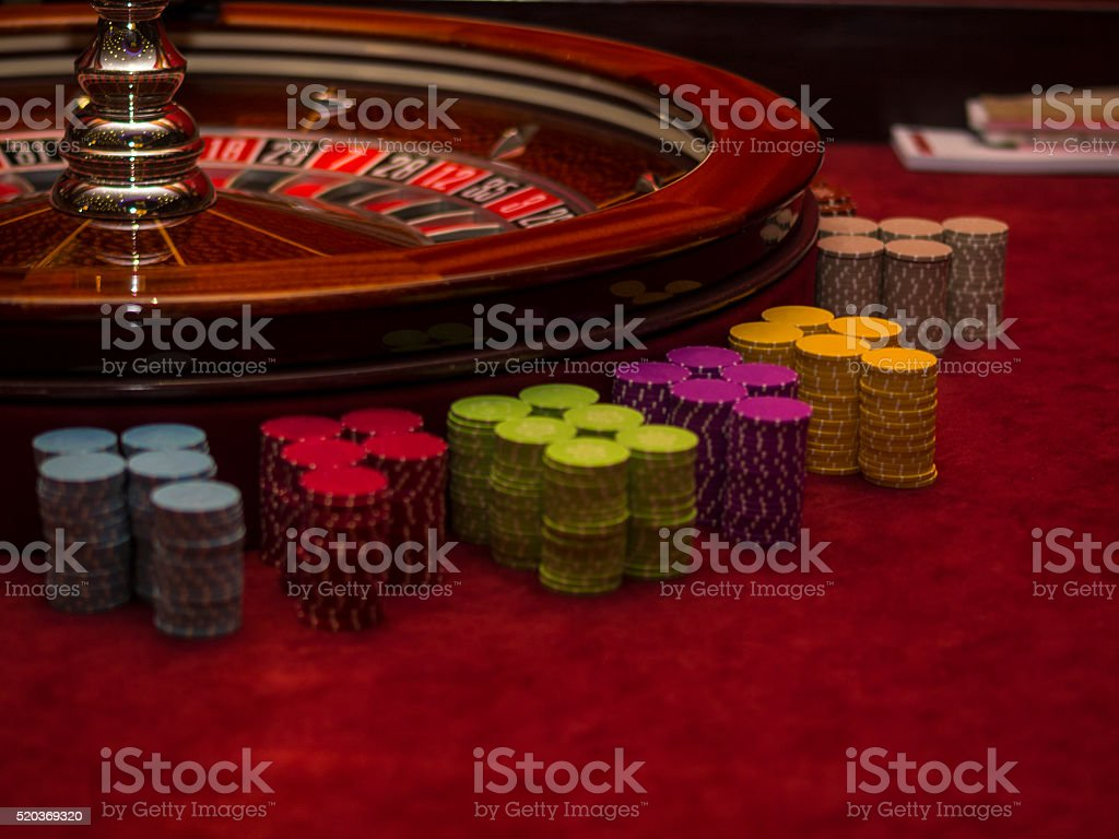 Roulette wheel with gambling chips in casino. stock photo