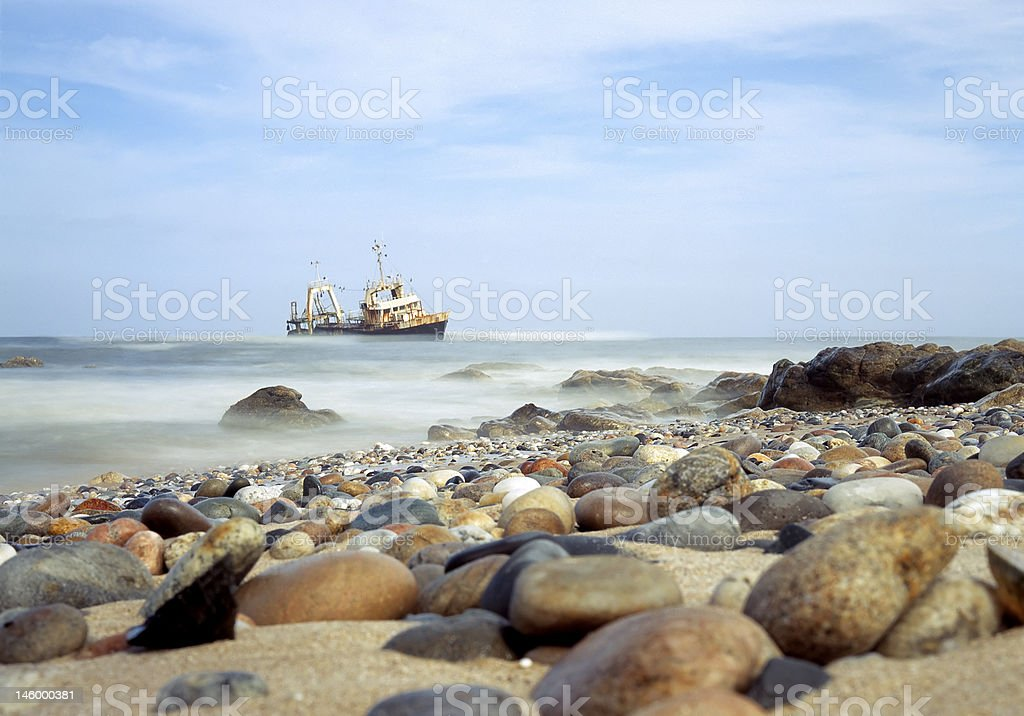 Round Beach Rocks With Shipwreck in the background, Namibia stock photo