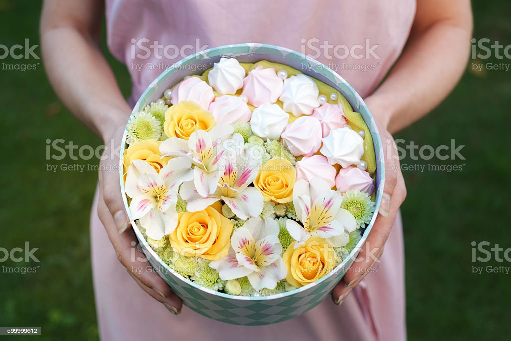 Round box with fresh flowers and meringue cookies stock photo