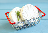 Round  camembert cheese mold  with rosemary in a shopping cart
