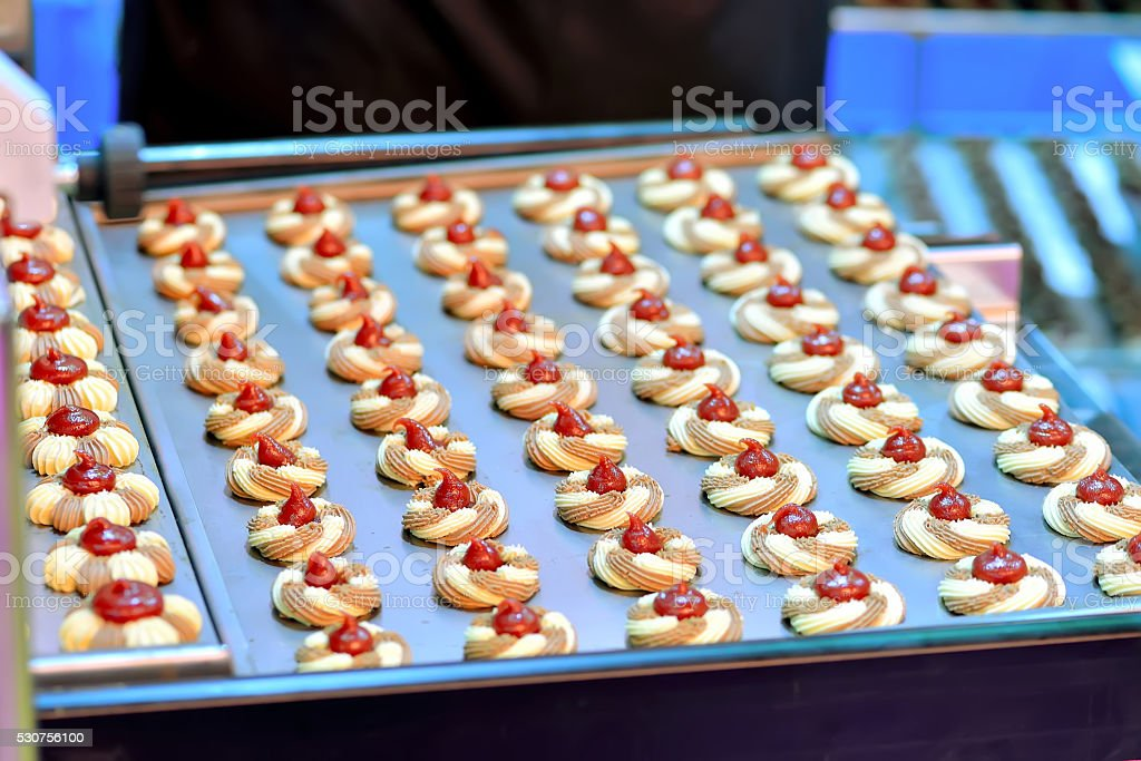 Round cookies with jam on confectionery production stock photo