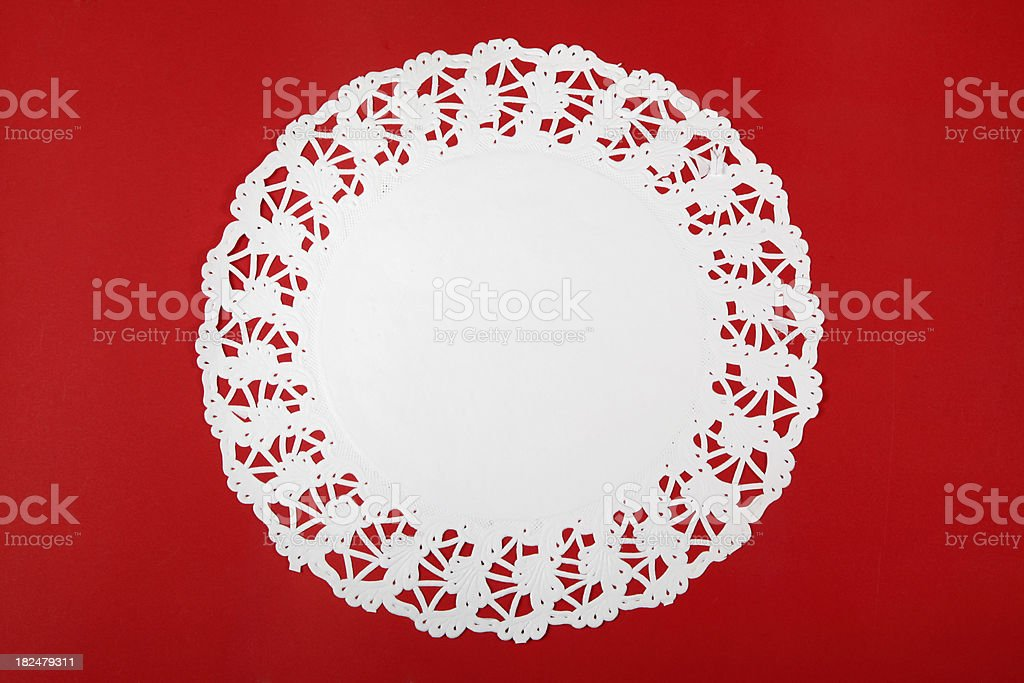 Round doily on red cardboard stock photo