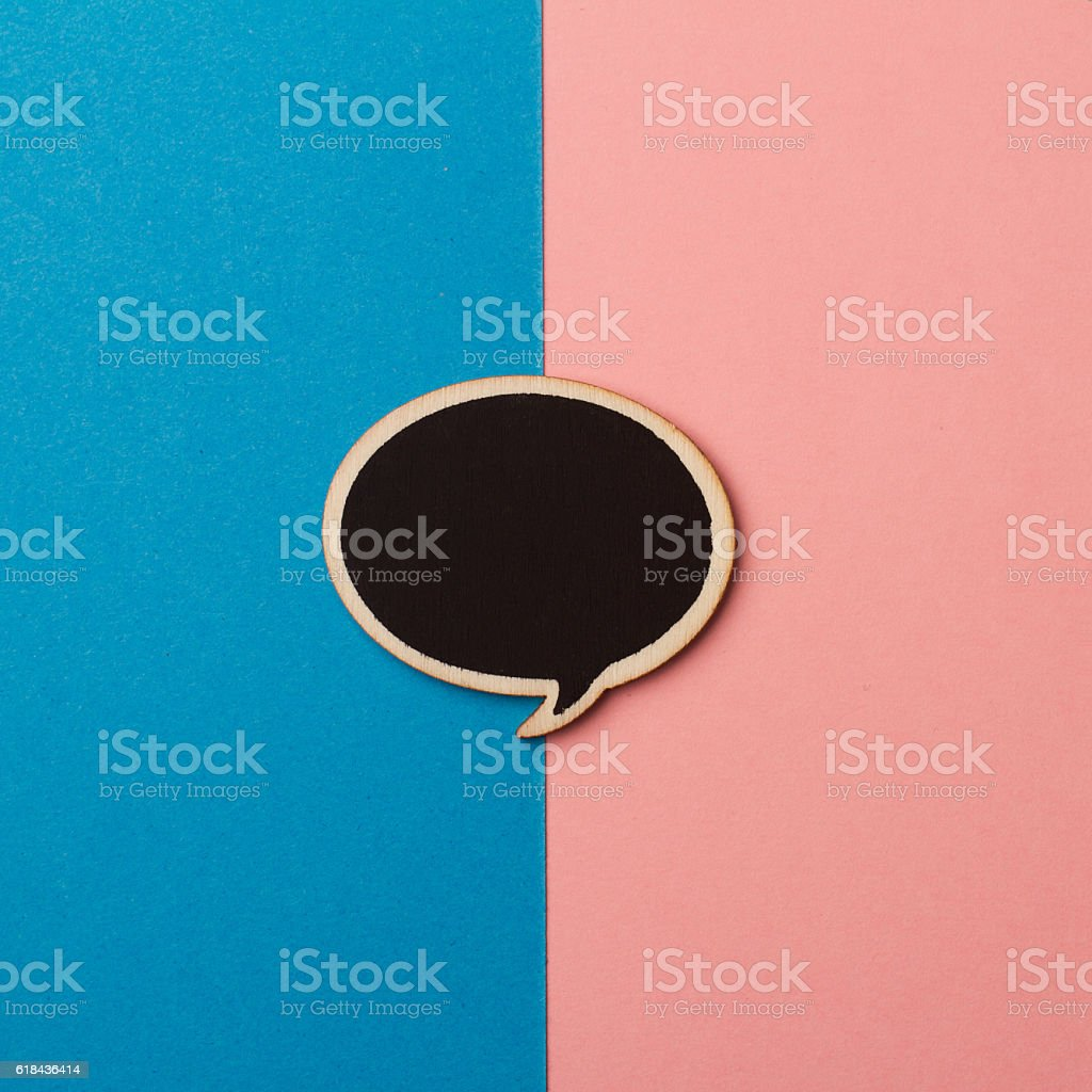 Round empty chalkboard wooden speech bubble on pink and blue stock photo