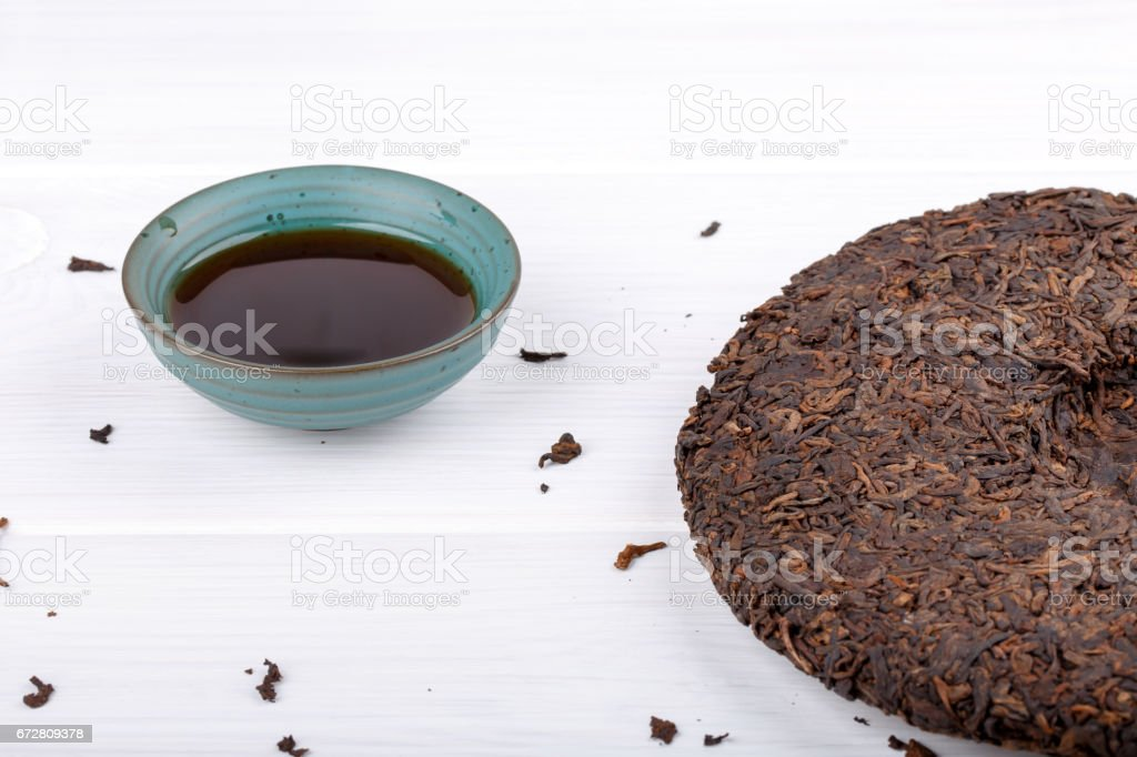 Round flat disc of puer tea and cup on white. Pressed Chinese fermented Pu-erh tea. stock photo