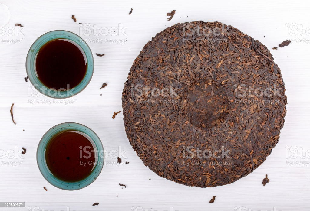 Round flat disc of puer tea and two cup on white. Pressed Chinese fermented Pu-erh tea. Top view. stock photo