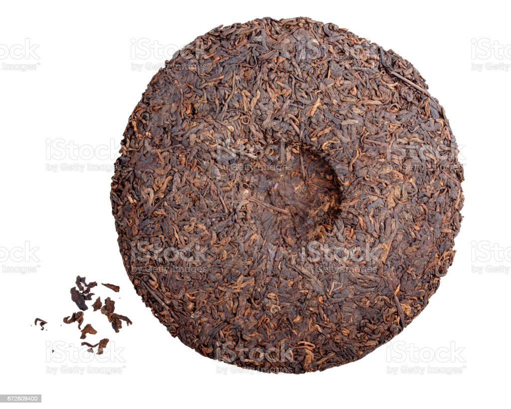 Round flat disc of puer tea isolated on white background. Pressed Chinese fermented Pu-erh tea. stock photo