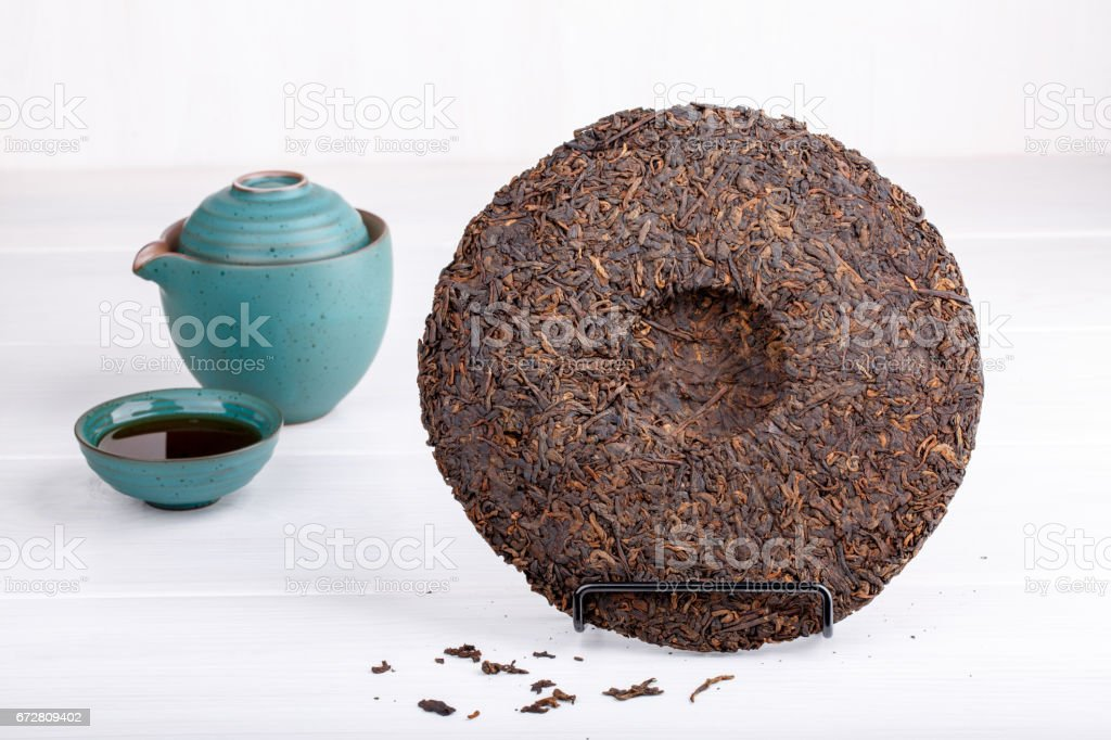 Round flat disc of puer tea on white. Pressed Chinese fermented Pu-erh tea. stock photo