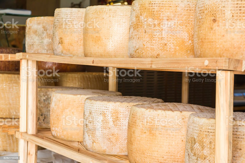 round forms of aged cheese for sale in local market stock photo