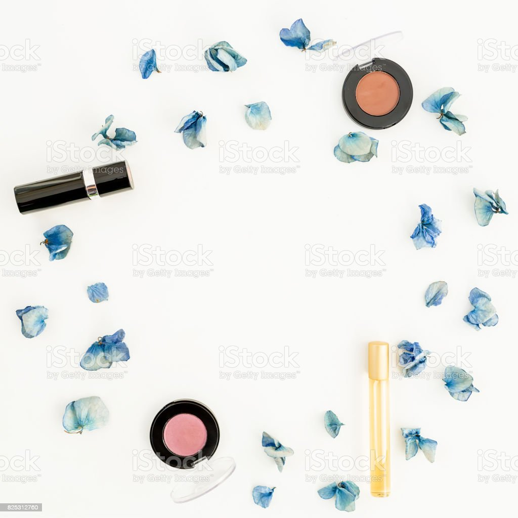 Round frame made of blue petals and woman cosmetic. Flat lay. Top view. stock photo