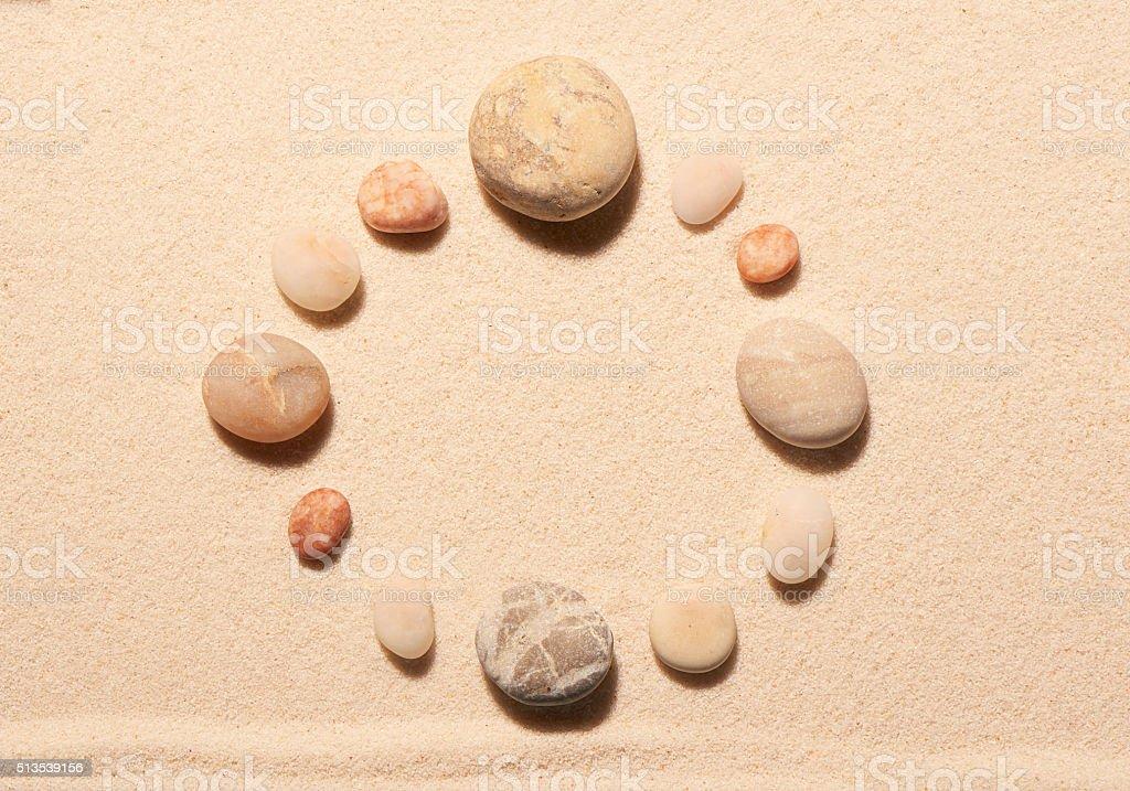 Round frame of sea stones on sand. Summer beach background stock photo