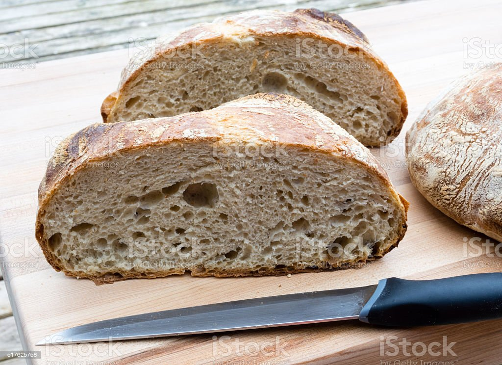 Round french boule bread cut in half with knife stock photo