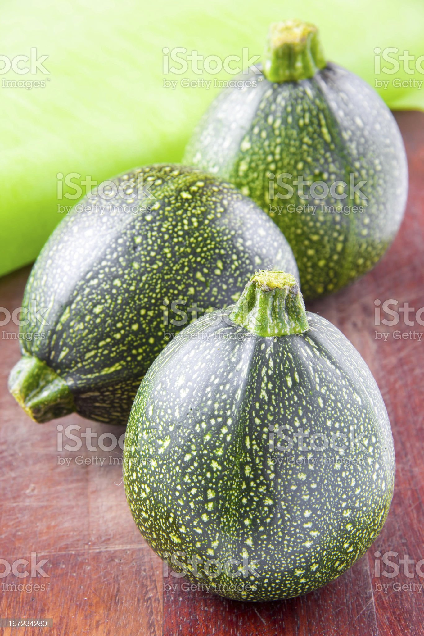 Round green zucchini on wooden table royalty-free stock photo