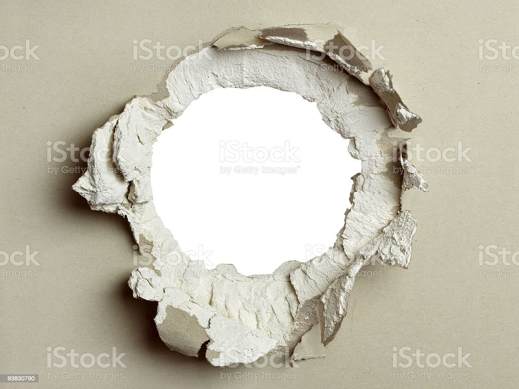 Round hole punched through a taupe wall stock photo