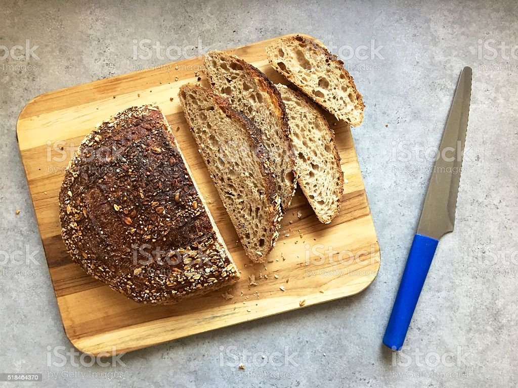 Round loaf of slow-fermented sourdough whole-grain bread with slices cut stock photo