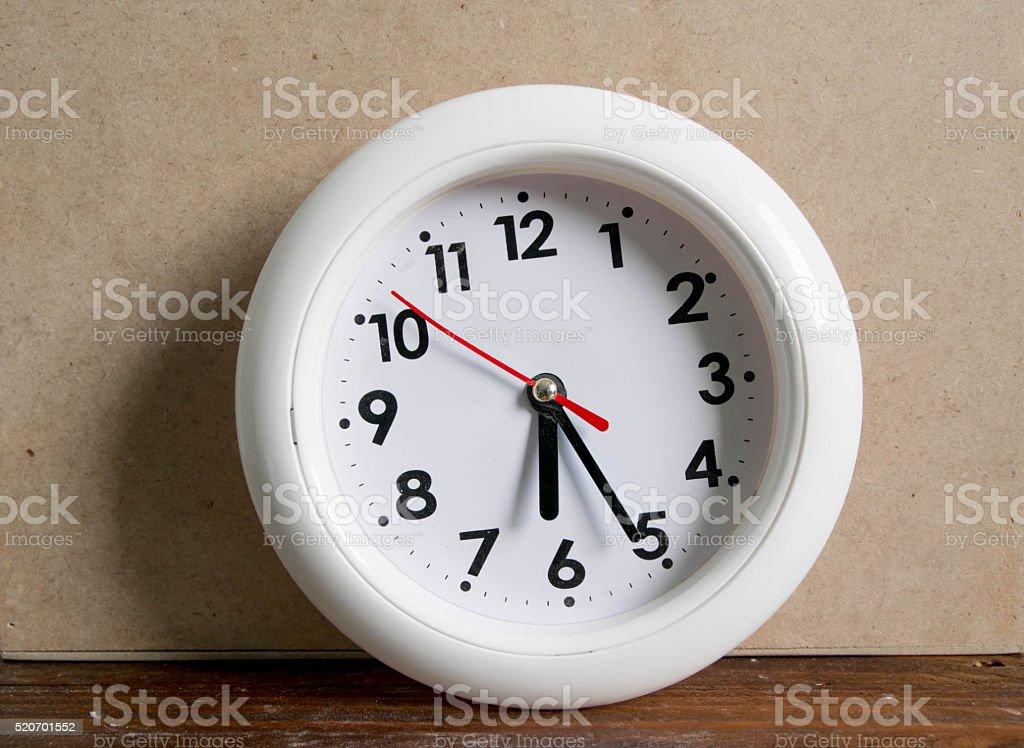 Round office clock showing six o'clock twenty five vintage stock photo