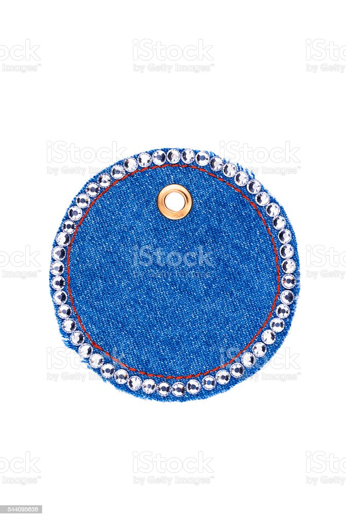 Round price tag encrusted with crystals made of denim, isolated stock photo