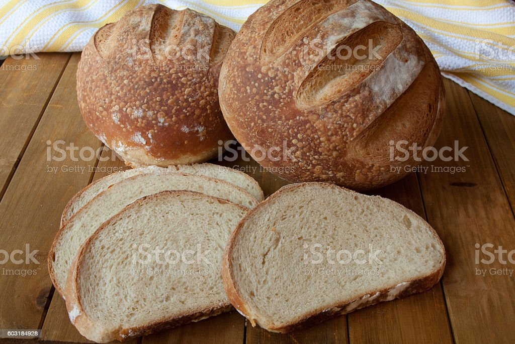 Round sourdough breads with bread slices stock photo