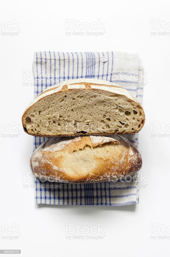 Round sourdough loaf on blue tea towel stock photo