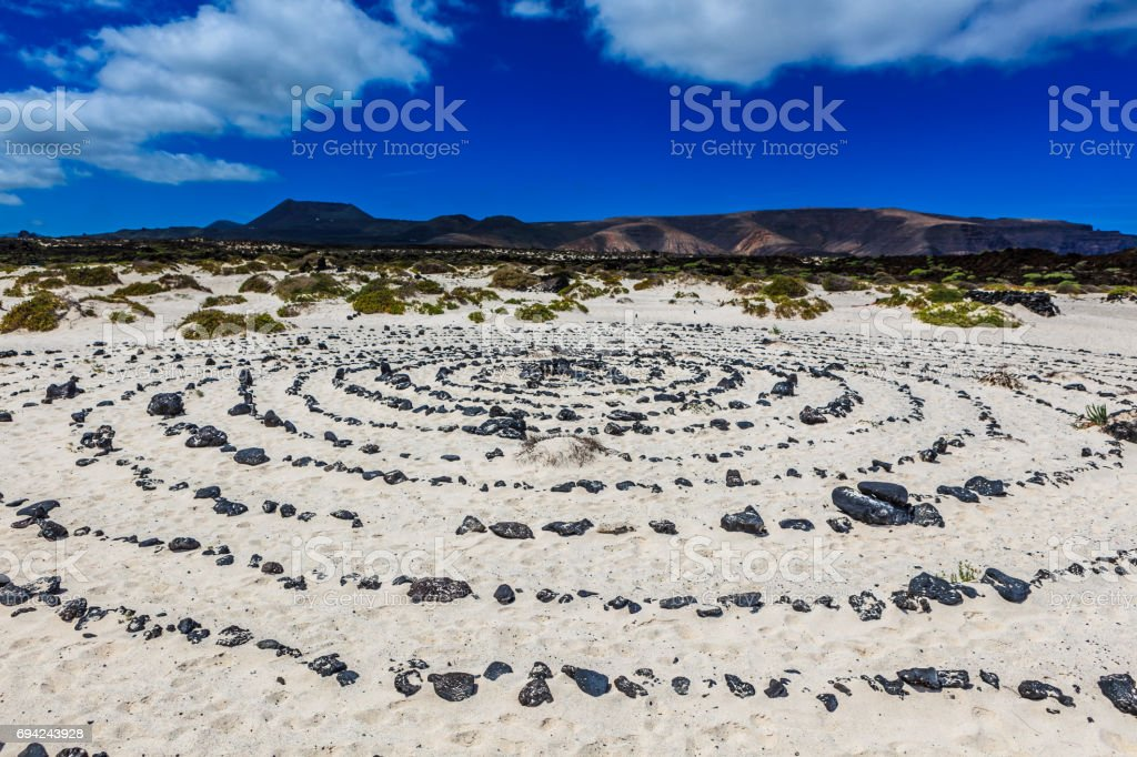 A round stone pattern in the sand by a beach stock photo