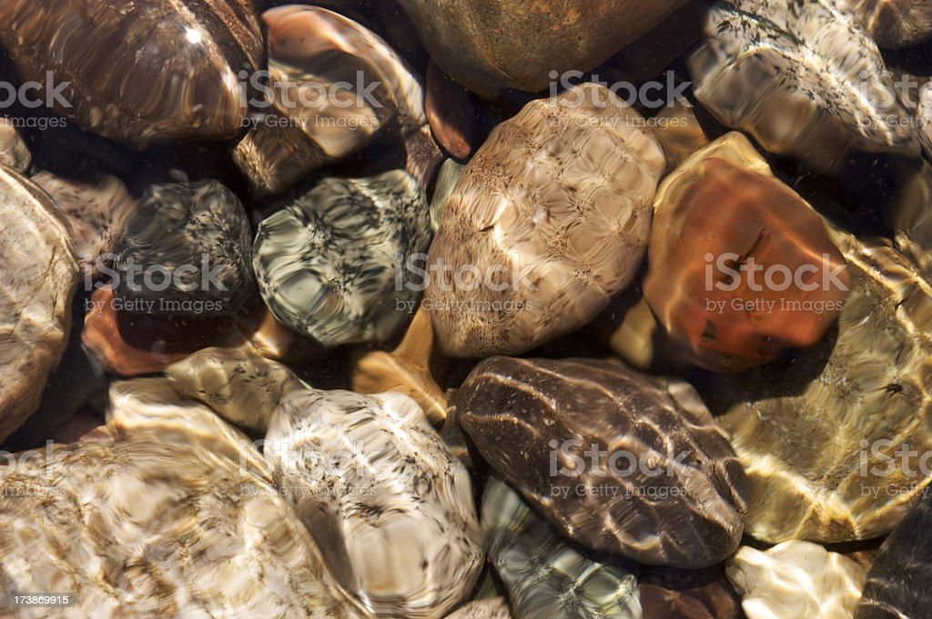 Round stones under water. Full frame royalty-free stock photo