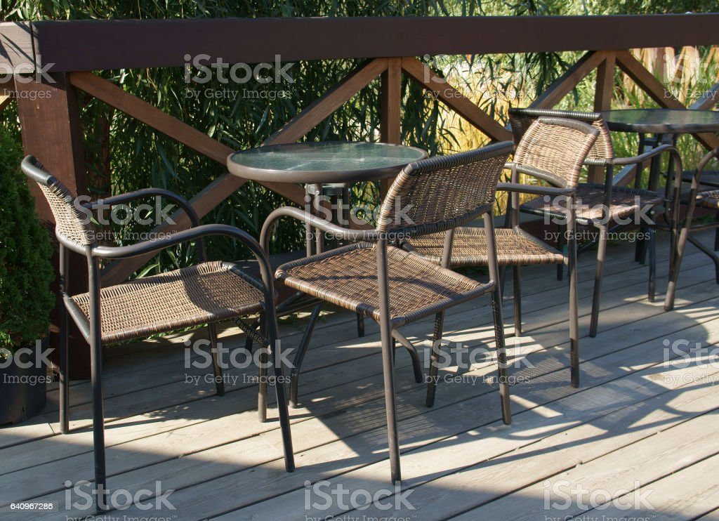 Round tables and wicker chairs stock photo