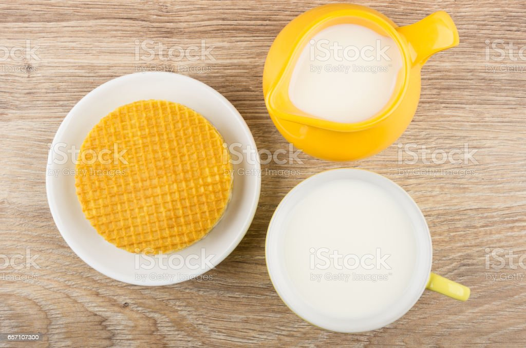 Round wafer with stuffed in saucer, milk in pitcher stock photo