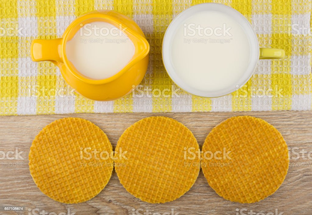 Round wafer with stuffed, milk in jug and cup on napkin stock photo