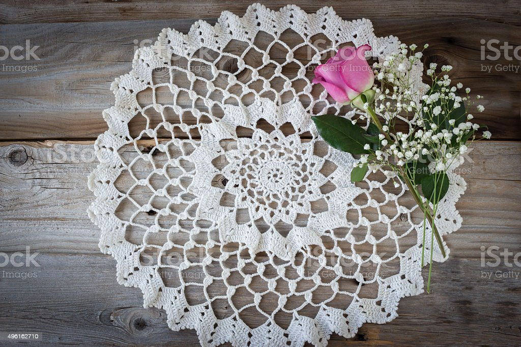round white doily on wood background with pink rose. stock photo