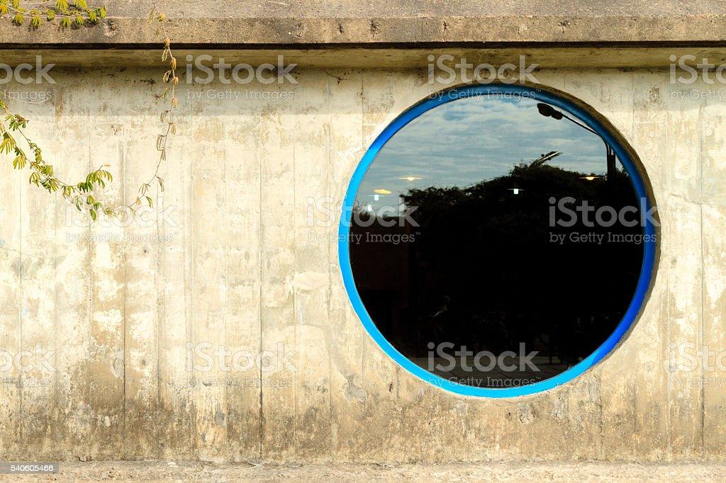 Round window on concrete wall stock photo