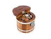 Round wooden money box with lock full with coins isolated